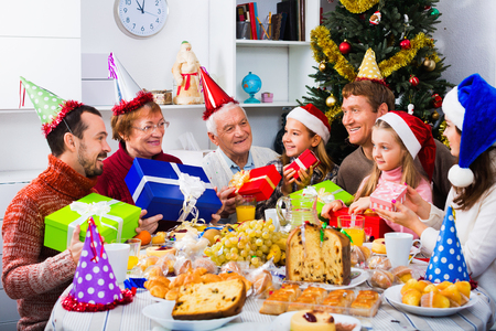 Large satisfied friendly  family exchanging gifts during Christmas dinner 스톡 콘텐츠 - 112059255