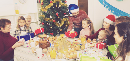 Smiling family members handing gifts to each other during Christmas dinner at home 스톡 콘텐츠