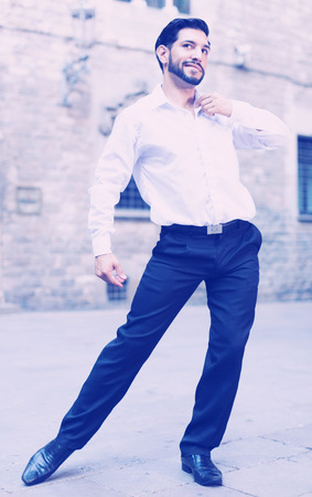 Handsome passionate man dancing alone outdoors against old stone castle Stock Photo