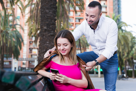 Girl is sitting with phone and inaccessibility for stranger man outdoors. Фото со стока