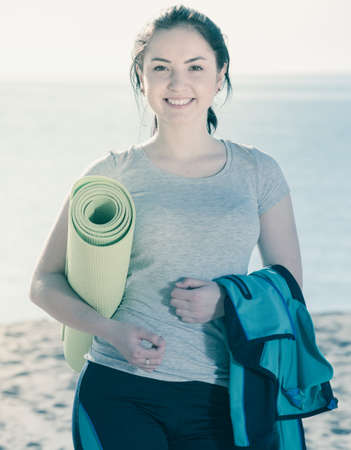 Smiling girl preparing for regular training on beach
