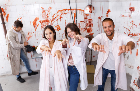 Group of cheerful young adults posing as zombies in stylized escape room with traces of blood