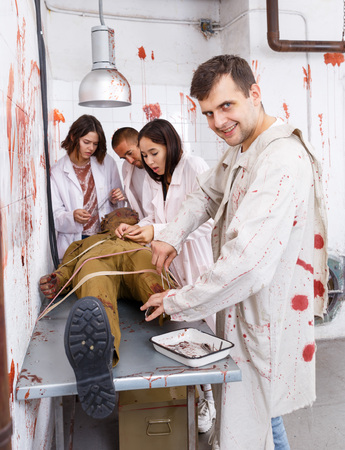 Guy with mad look standing over zombie mannequin with friends in quest room styled as abandoned surgical room with blood traces Stock Photo
