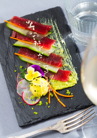 Slices of raw tuna sashimi served on black board with cucumber and sauce of avocado Stockfoto