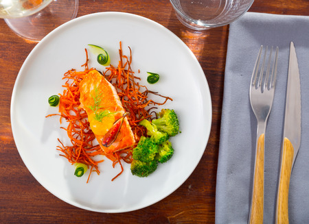 Delicious roasted salmon on pillow of smoked carrots served with fresh vegetables on plate Stockfoto