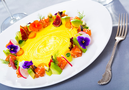 Image  of delicious  ring from tartare of  salmon with avocado, fig and vegetables,  served with flowers