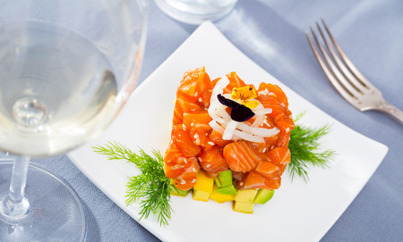 Fish tartare with raw salmon and diced avocado in shape of colorful cube decorated with pansy on white plate 免版税图像