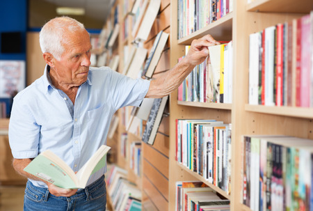 Aged man interested in books looking for necessary literature on shelves of bookshop Foto de archivo
