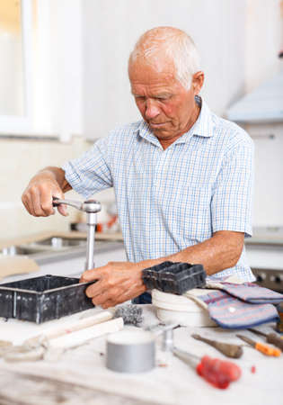 Skillful older man engaged in renovation work indoors Banco de Imagens