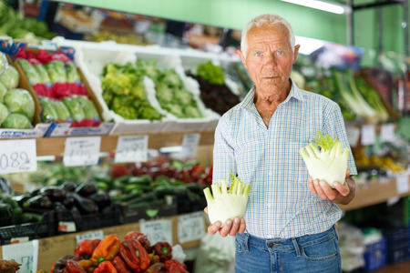 Senior man searching for fresh vegetables while shopping in greengrocery Foto de archivo