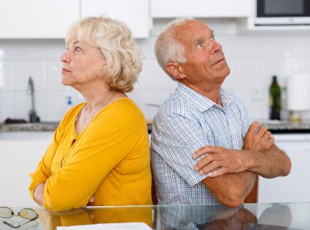 Portrait of upset mature couple discussing, quarrel at home interior