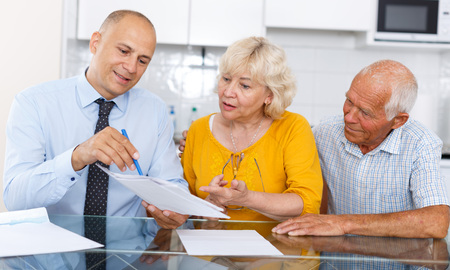 Aged couple signing financial agreement with bank worker at home