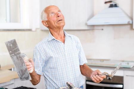 Senior man working on his house overhaul, determining scope of plastering works indoors