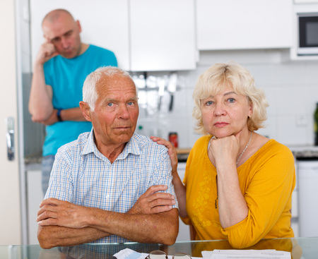 Upset mature parents discussing after quarrel with son on background Stock Photo