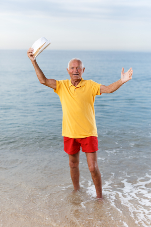 Active satisfied mature man posing near ocean alone