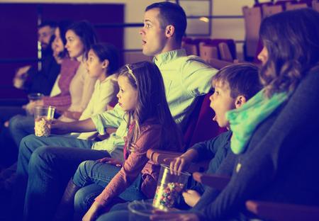 영화관에서 흥미진진한 영화를 보는 젊은이들