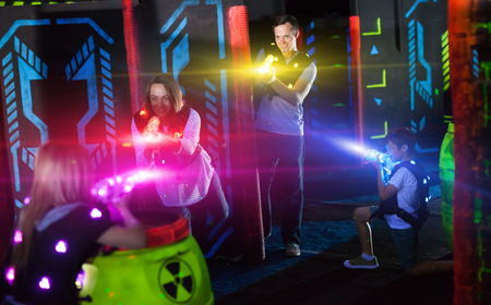 Modern young parents and children playing laser tag in dark labyrinth in bright beams of laser pistols Imagens