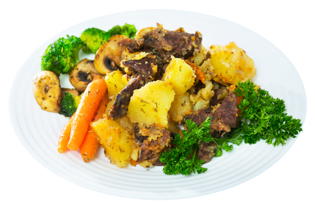 Homemade stew with beef and vegetables, mushrooms and greens. Isolated over white background