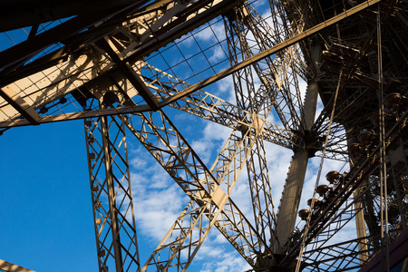 Architecture of Eiffel Tower. Closeup view of metal frames, beams, rivets against blue sky as background Imagens
