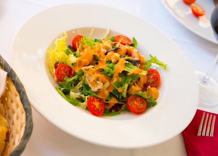 Appetizing sea salad with Seafood Cocktail, lettuce, cherry tomatoes and pink sauce Stockfoto