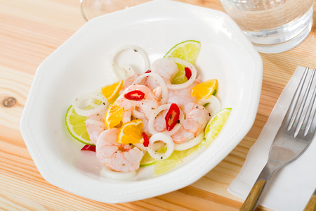 Exotic shrimp ceviche served with sliced lime, mandarine, fresh onion and chili pepper