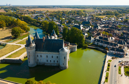 Aerial view of countryside of commune of Sully-sur-Loire with medieval fortified castle, France