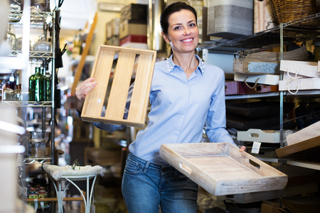 Positive female standing with wooden box in decoration and furniture store Archivio Fotografico