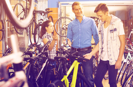 positive father with teenage son getting help from female seller in bike store. Focus on man