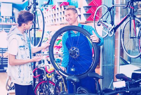 caucasian man seller in uniform talking to customer while fixing bike wheel in sport hypermarket