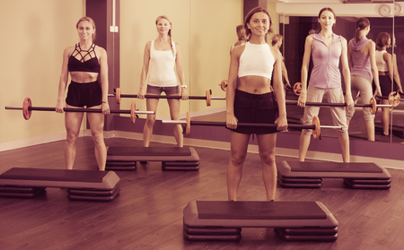 Group of young women training with barbell workout at fitness center