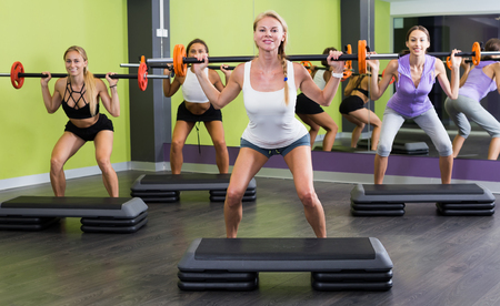 Group of smiling girls training weight lifting workout at fitness center Stock Photo
