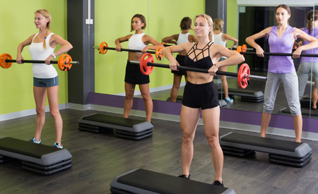 Group of females performing weight lifting workout at gym Stock Photo