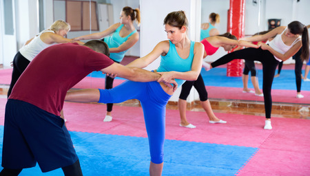 Glad  positive  female is training self-defence moves in pair with trainer in sporty gym.