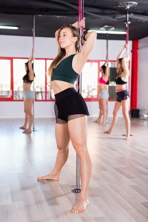 Femmes positives gaies sexy pratiquant la danse de poteau dans le studio de forme physique