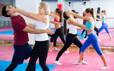Sporty cheerful positive mature woman with her instructor are training self-defence moves in gym.