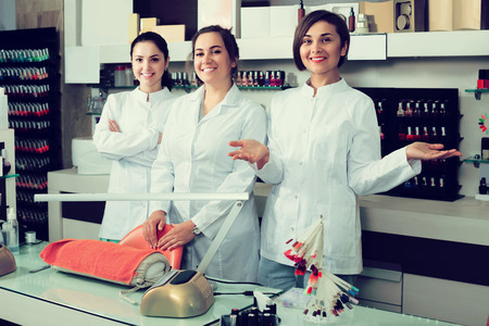Portrait of happy american professional manicurists at working place inviting to salon