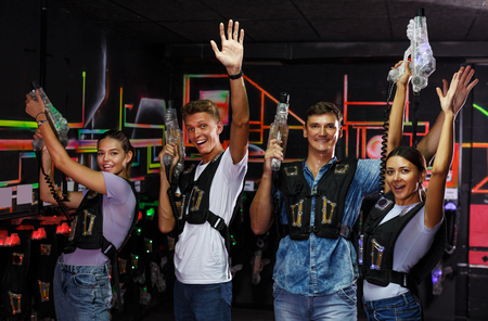 young happy people with laser guns having fun together in dark labyrinth 版權商用圖片