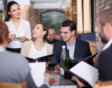 Employee waitress woman taking order from positive guests at restaurant