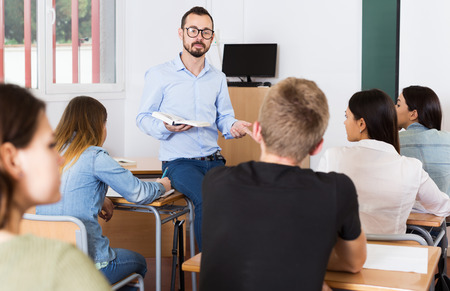 Positive male teacher is giving interesting lecture for students during lesson in the classroom