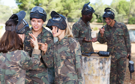 Two positive female paintball players listening instructor before playing outdoors Banco de Imagens