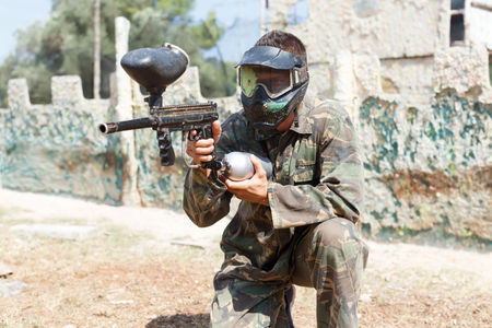 Adult male paintball player aiming and shooting with gun at opposing team outdoors