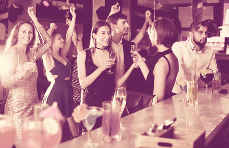 Young females and males celebrating corporate in the bar at night Stock Photo