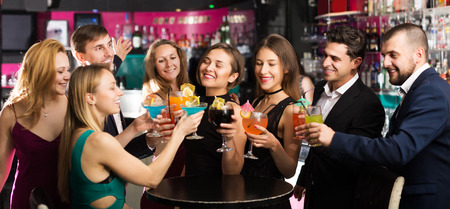 Cheerful females and males celebrating corporate in the bar at night