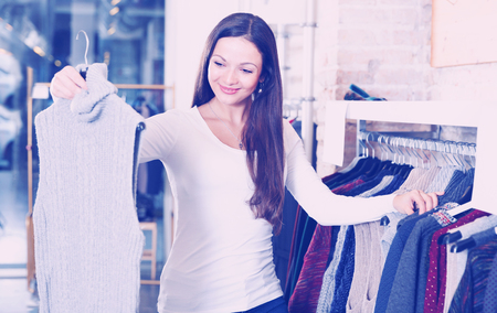 Portrait of adult woman choosing sweater in the modern shop