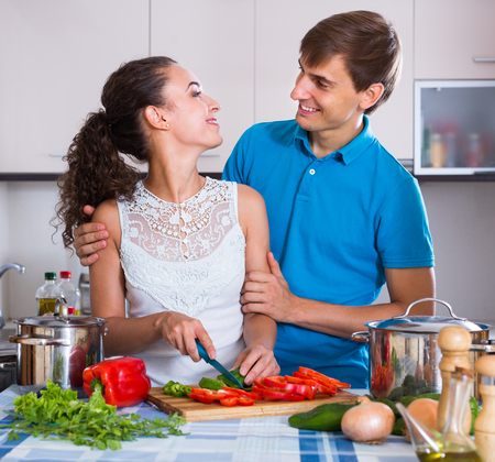 Young husband helping european wife to prepare healthy dinner