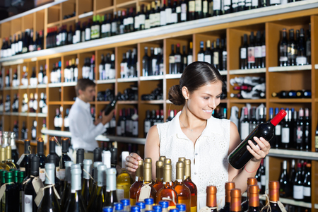 portrait of smiling young woman selecting bottle of wine in wine store