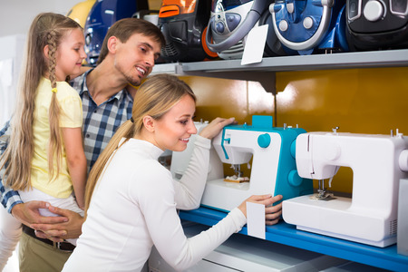 portrait of joyful family selecting modern sewing machine in appliance store. Focus on woman