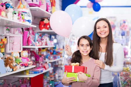 positive woman and daughter with gifts and balloons in the toys shop Reklamní fotografie