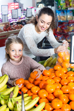 Cheerful young woman and little girl purchasing sweet tangerines at market Standard-Bild