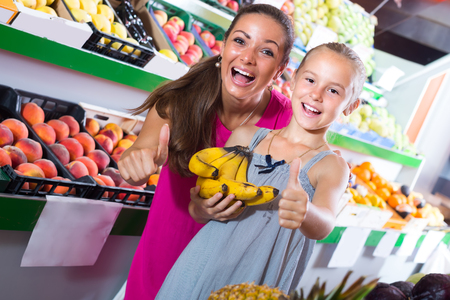 portrait of happy smiling young woman with daughter looking excited on fruit market